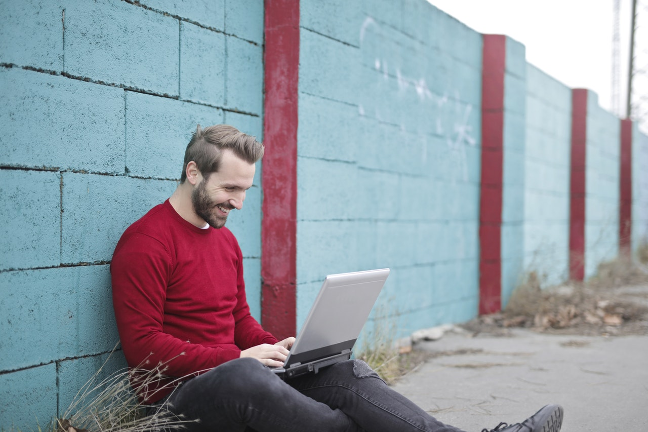lende man sitter ute vid en bärbar dator