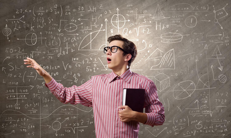 Hämmästyneen näköinen mies ojentaa kättään liitutaulun edessä, jolla matemaattisia symboleita.