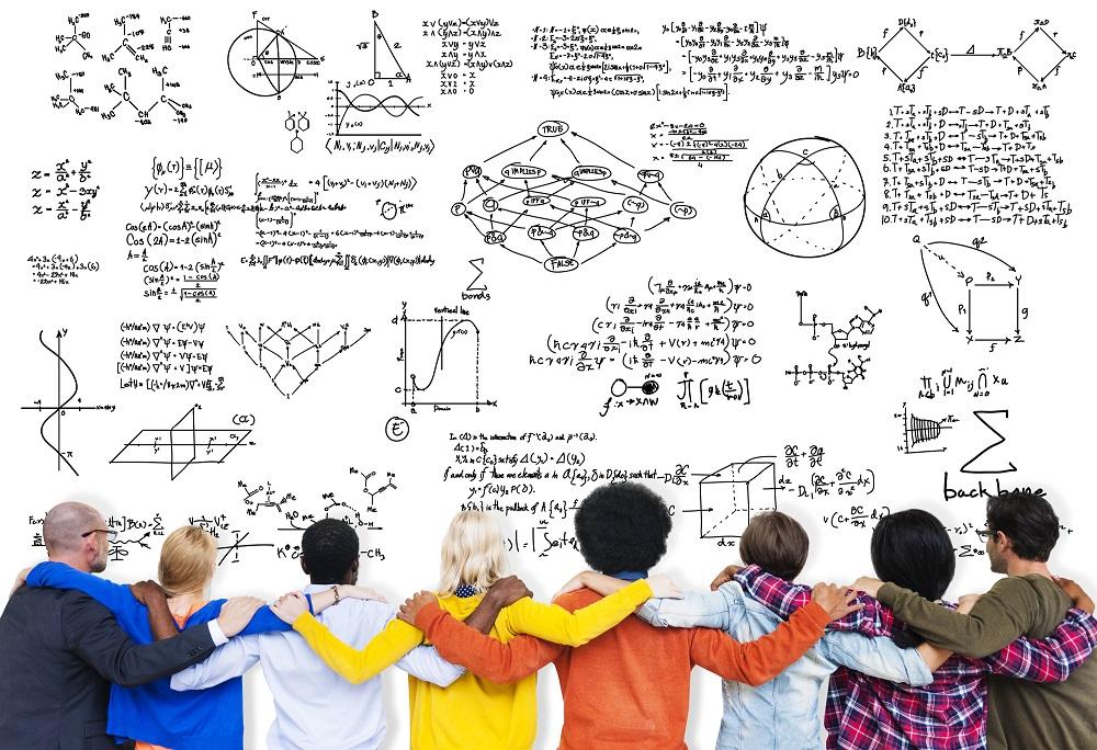 ihmisiä yhdessä tutkimassa matemaattisia kaavoja