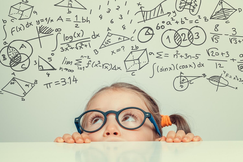 Silmälasipäinen tyttö kurkistaa matemaattisia symboleita