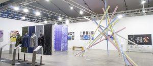 Näyttelyesineitä. Esimerkiksi postereita, vaatteita, geometrinen rakennelma.