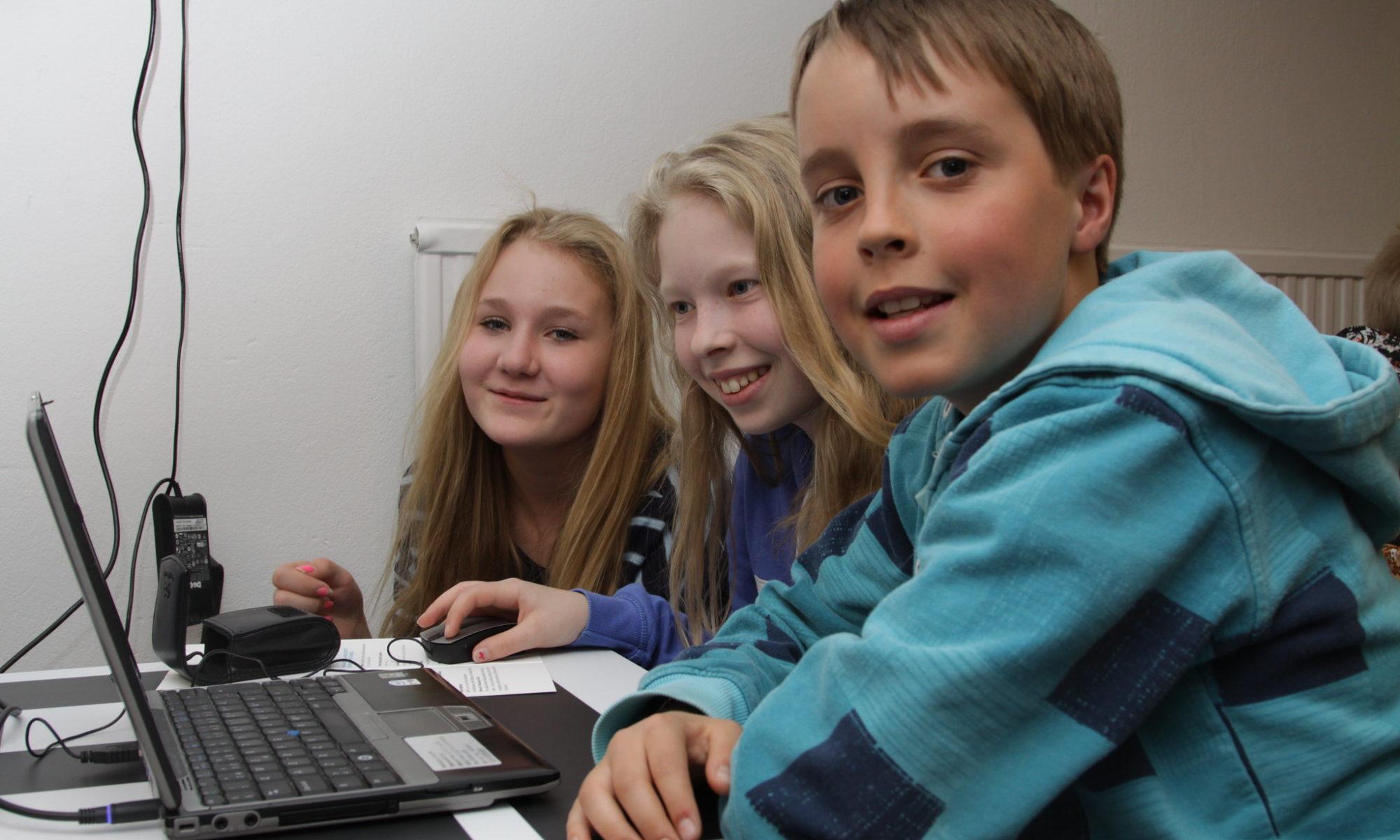 kolme iloista lasta tietokoneen ääressä