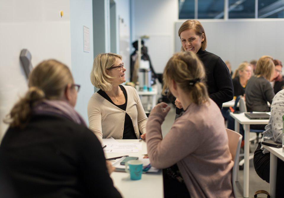 koulutukseen osallistujia istuu luokkatilassa, opettaja ja osallistujat hymyilevät toisilleen